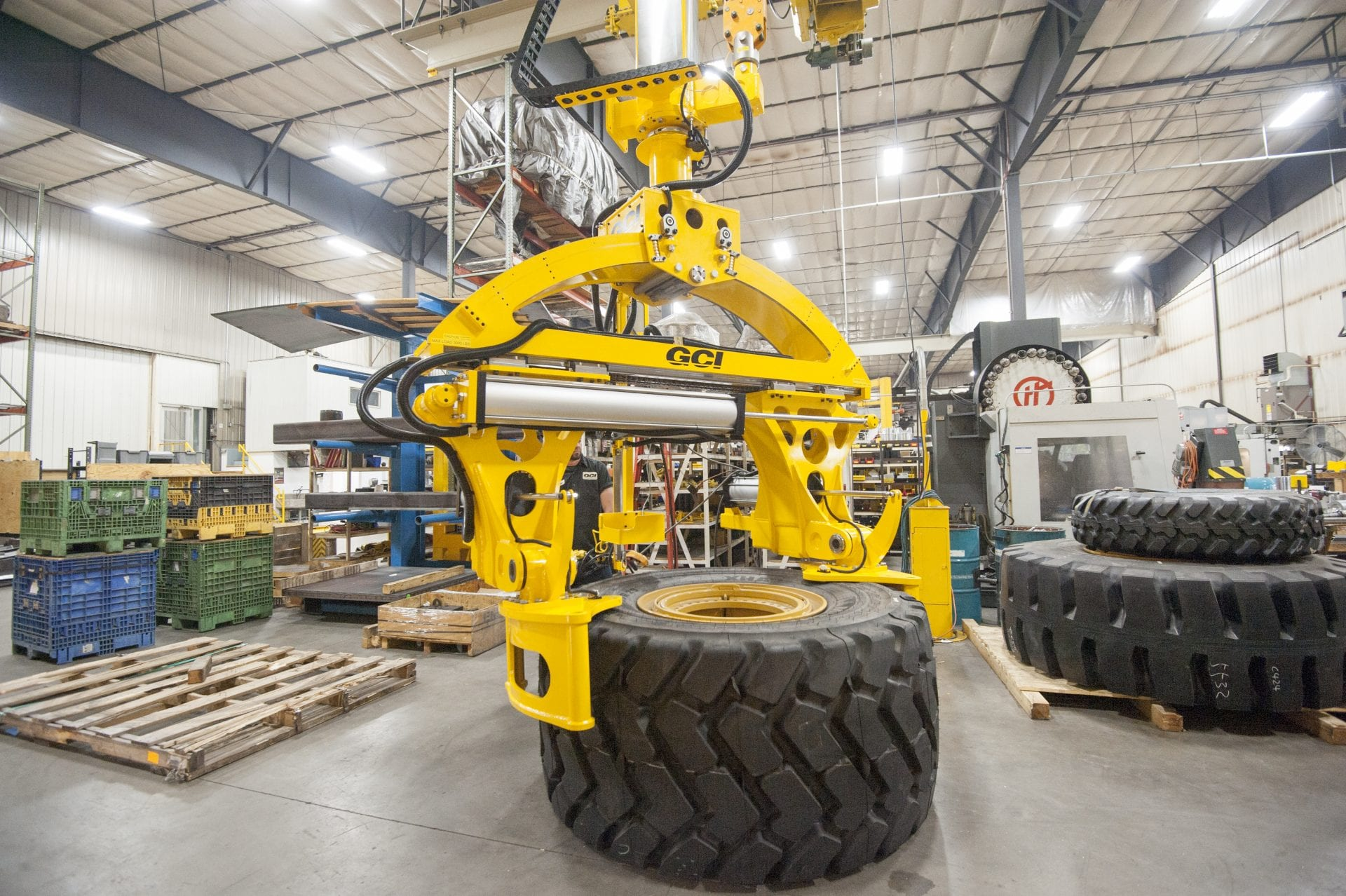 Overhead mount GCI manipulator lifting 3,000 lb Caterpillar tires of varying sizes