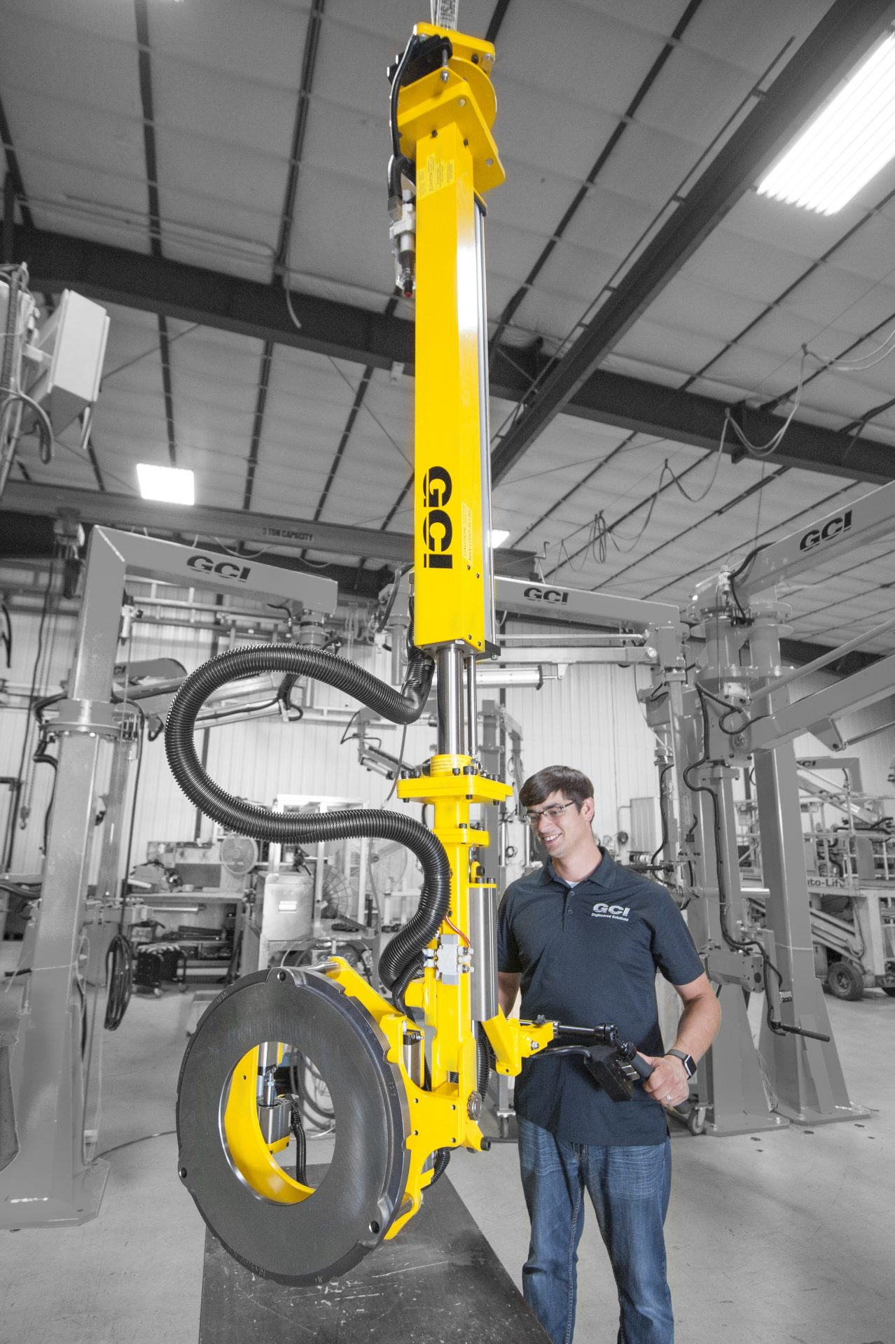 Operator lifting a backing plate with an overhead manipulator