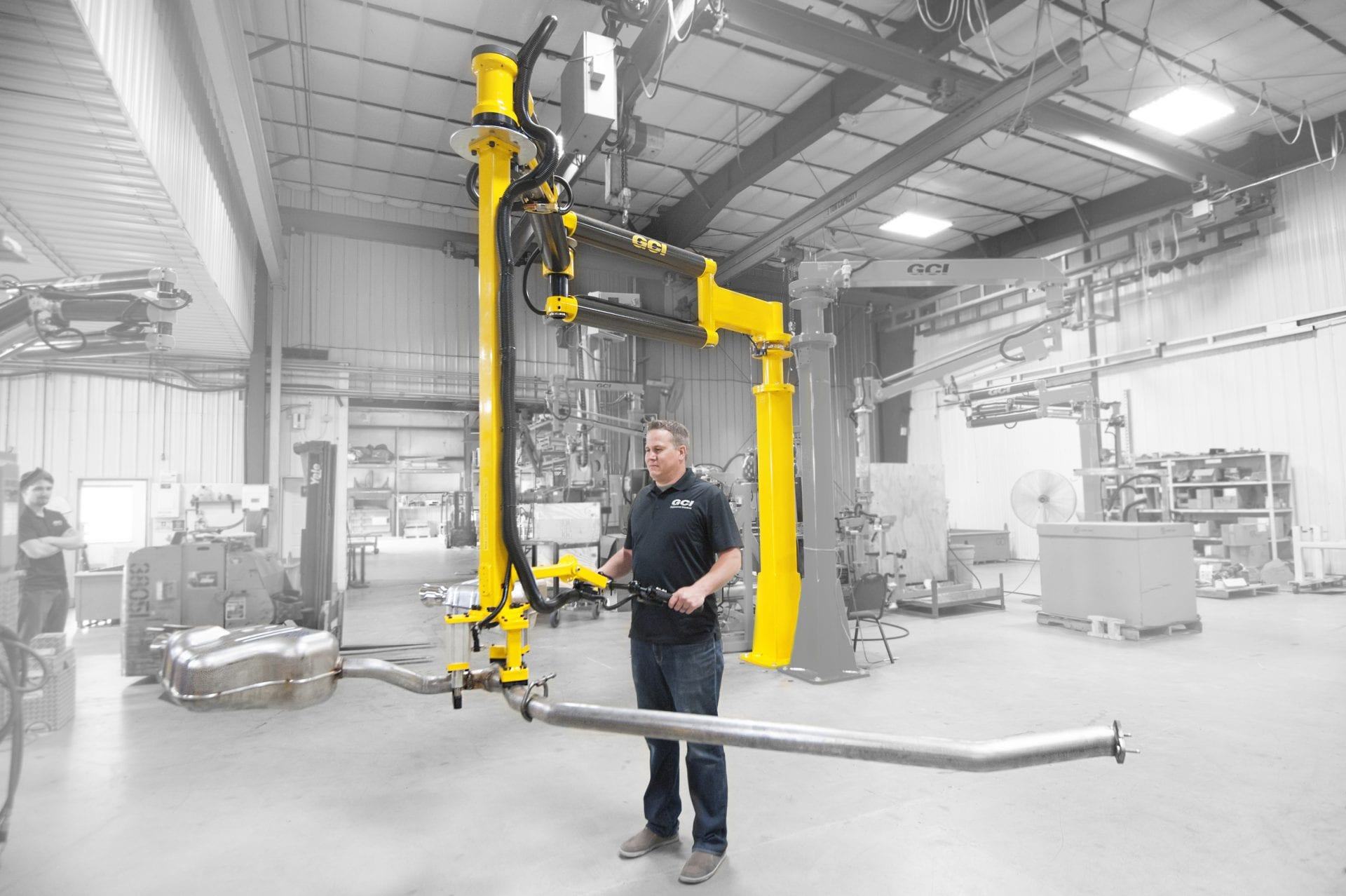 Man lifts heavy exhaust with a GCI industrial manipulator